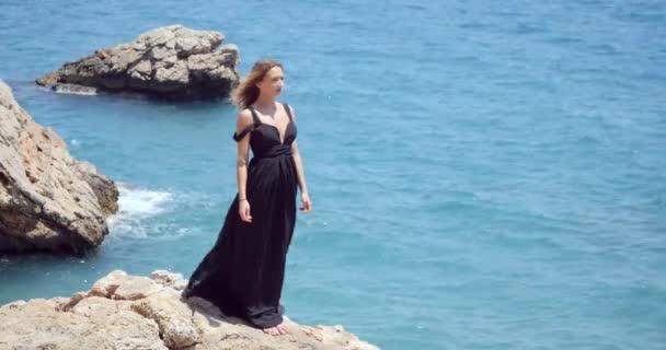 Krásná žena v elegantních černých šatech u moře