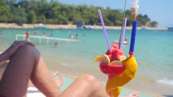 Man relaxing on the beach with fruit coctail