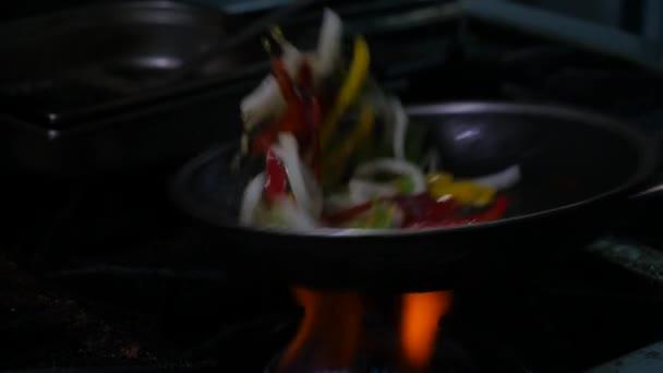Profesionální kuchař a požár. Vaření zeleniny a potravin na otevřeném ohni na tmavém pozadí