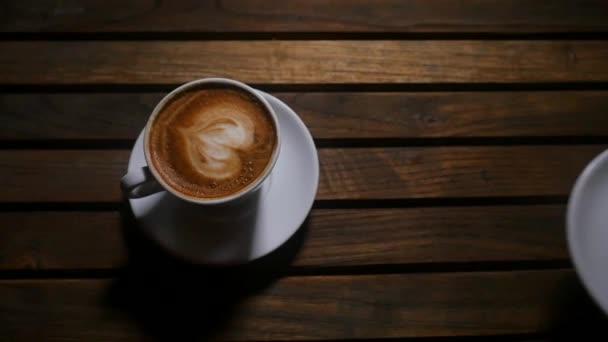 Fehér csésze kávé felett fa háttér