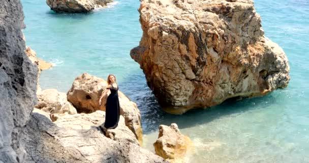 junge hübsche Frau im schwarzen Ausschnitt elegantes Kleid sitzt in der Nähe des Meeres