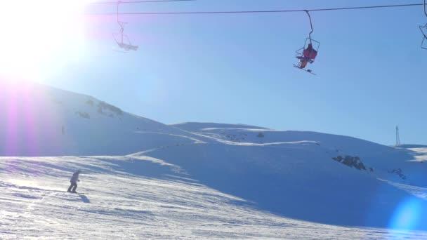 Pohled na pohyblivé lyžařské vleky s lidmi a sportovskými snowboardisty od zasněžené hory na pozadí