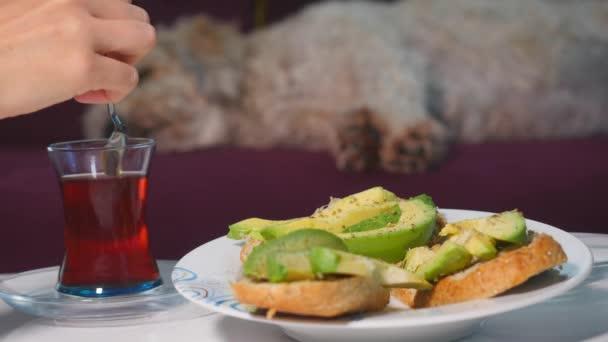 Ženy mají snídani s avokádovými sendviči a červeným čajem