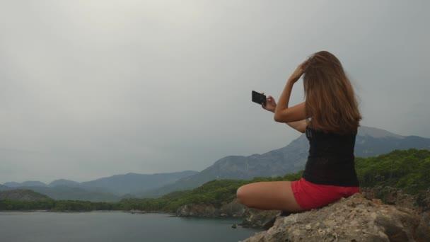 Ženská turistka sedící na skále na jasném nebi a klidné mořské pozadí