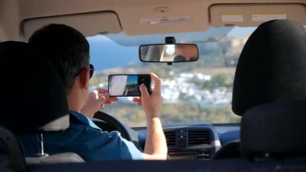 Rückansicht des jungen Mannes im Auto sitzen und Fotos von schöner Aussicht