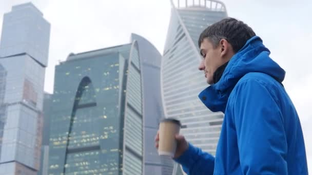 Young man with coffee on Moscow new city background