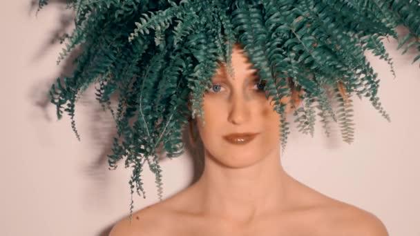 Krásný portrét mladé ženy se zelenými lístky na kapradí.