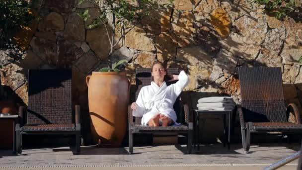 Mladá žena v županu na soláriu venku