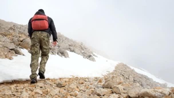 Hikers walking outdoors wearing hiker backpacks.