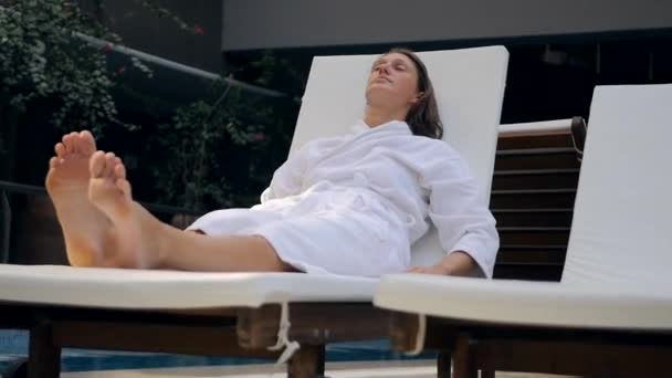 Young woman in bathrobe on the sunbed intdoors