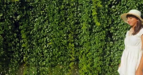 Beautiful woman sending a kiss on the wild grape wall background