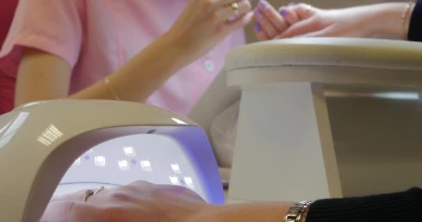 Nahaufnahme einer UV-LED-Lampe mit einer weiblichen Hand im Inneren der Befestigung der Gel-Nagellack.