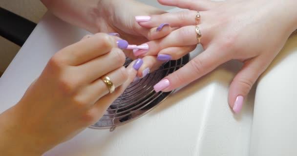 Mistr manikúry aplikuje gelový lak na růžovou barvu