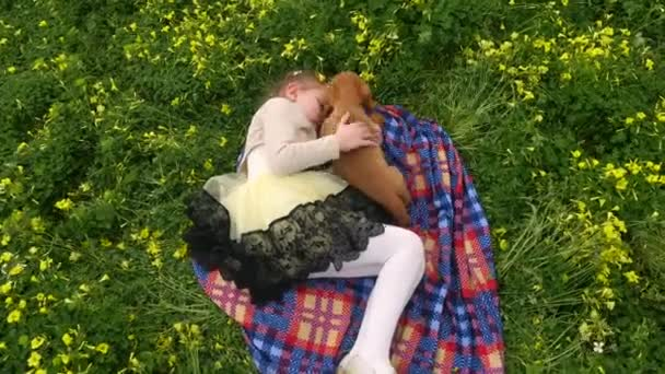 Hübsches Mädchen auf grünem Gras mit einem Welpen