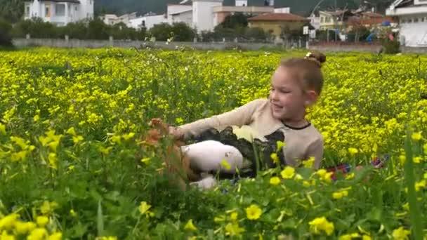Schönes Mädchen spielt auf grünem Gras mit einem Welpen