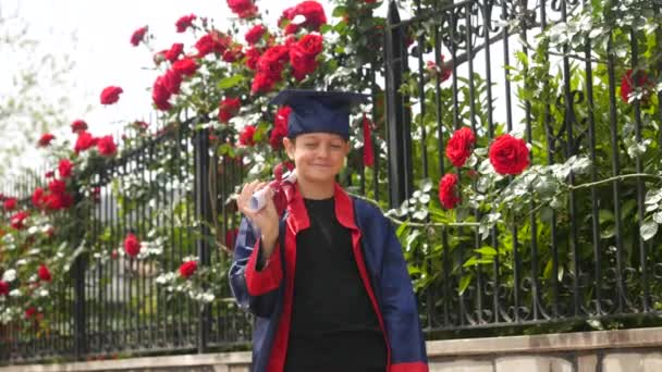 Happy caucasian child in graduation gown with diploma standing near stone fence full of wild roses