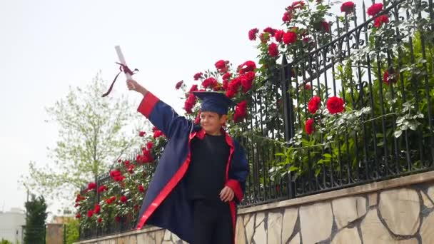Happy caucasian child in graduation gown with diploma joyfully dancing near fence full of wild roses