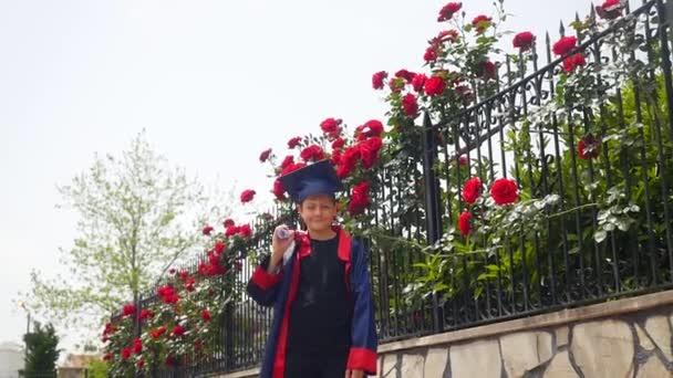 Šťastné kavkazské dítě v maturitní róbu s diplomem s radostným tancem u plotu plném divokých růží