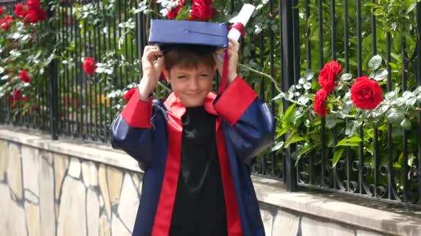 Šťastné kavkazské dítě v maturitní róbu s diplomem stojící blízko kamenného plotu plného divokých růží