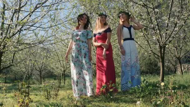 Young beautiful women in long dresses between spring blossom trees.