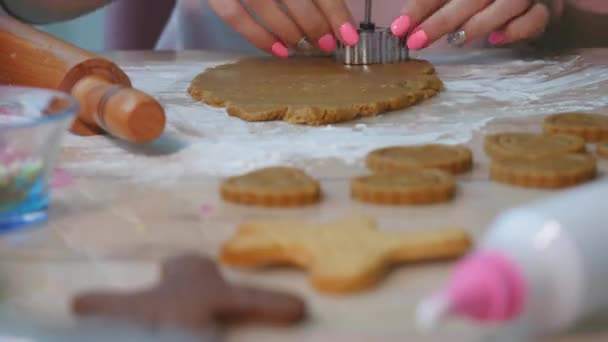 Fast motion of young woman rolling out tasty homemade Christmas cookie dough.