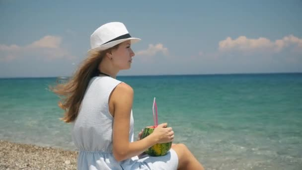 junge schöne europäische Mädchen mit weißem Hut trinken frische Fruchtcocktails am Strand