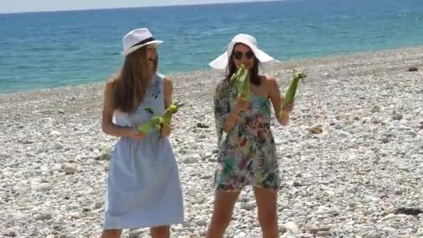 Mladé šťastné ženy vydělávají obilí v rukou a tančí legrační tanec na pláži