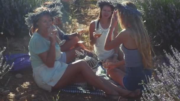 Čtyři mladé ženy mají piknik s vínem na levandulovém poli.
