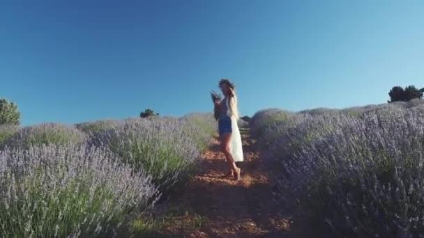Mladá žena v neformálním oblečení stojící na levandulovém poli