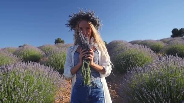 junge Frau im Kranz mit Blumenstrauß im Lavendelfeld