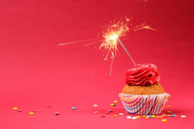 cupcake with sparkler on a colored background. Background for the holiday, birthday