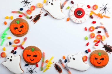 Halloween background with gingerbread and other sweets top view with place for text