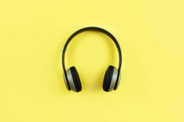 Fashionable headphones on yellow background. Music concept.