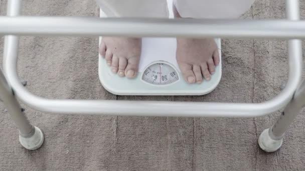 Eldely žena stojící na hmotnost scale, její váha měří 54 kg