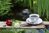 Photo Roses and Coffeebeans on a wooden bord in a garden