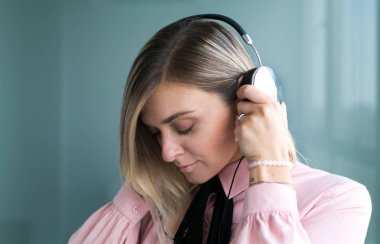 Beautiful blonde in silver headphones listens to music. Stylish