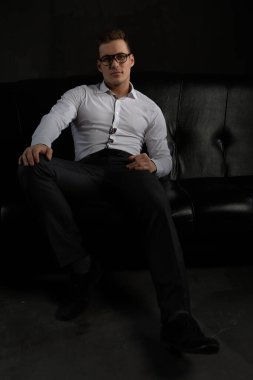 A brutal well dressed man is sitting on a black sofa