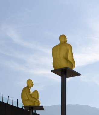 Two sculptures of a golden man sitting.