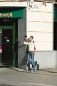 fiatal férfi állandó, a nap megvilágított utcai kamera