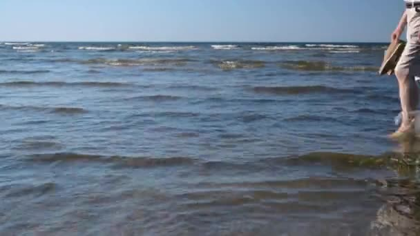 Mann läuft auf flachem Wasser von rechts nach links am Meer am Sandstrand
