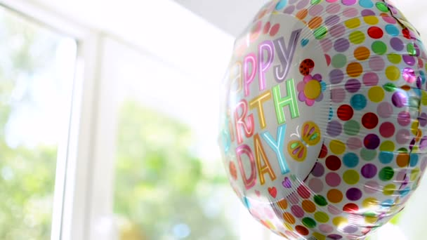 Happy Birthday celebration balloon with colorful reflections is slowly rotating