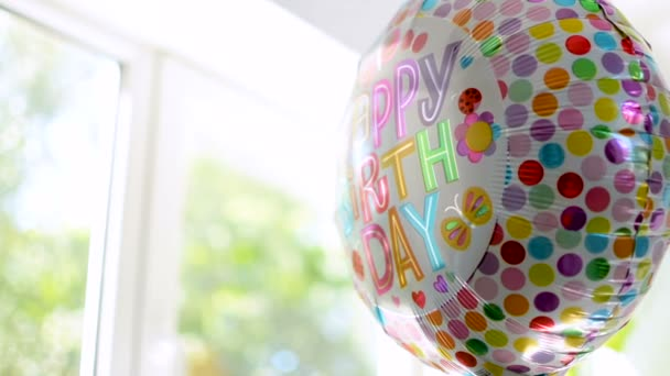 Close-up of party Happy Birthday helium baloon agains bright sunny background