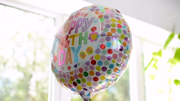 Happy Birthday party balloon reflecting surroundings with vibrantly printed text
