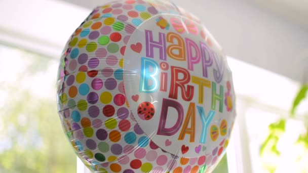 Closeup of helium inflated balloon with Happy Birthday text reflecting the light