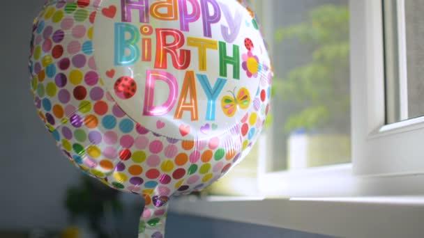 Happy Birthday party celebration balloon at window rotating reflecting sunlight