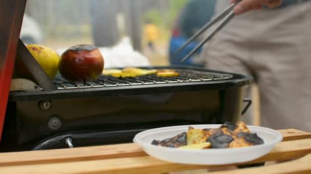 Hořel bramborové lupínky a vařená jablka closeup během rodinné grilování gril venku