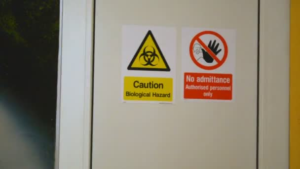Caution Biological Hazard and No Admittance warning danger signs on the door entrance to the laboratory