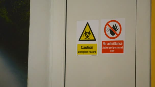 Zoom in on Caution Biological Hazard and No Admittance warning danger signs on the door