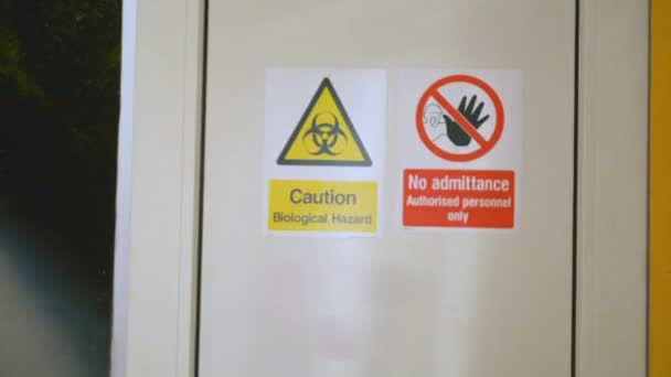 Scientist enters and leaves bio laboratory, warning sign Biological hazard on the door