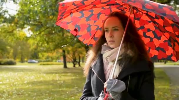 wunderschöne Dame mit großem roten Regenschirm spaziert im Park im goldenen Herbst